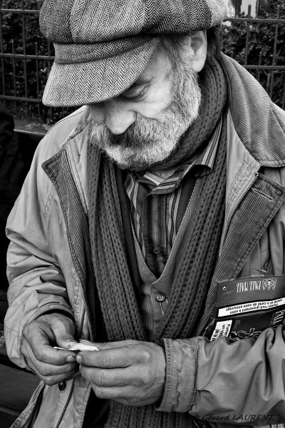 Claude Vasseur se roule une cigarette place des abbesses 75018